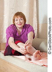 woman looks at her toenails