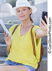 mature woman making a self portrait outdoors