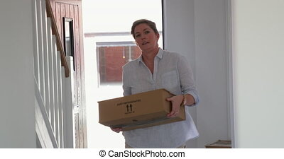 Mature Woman Moving Home - Mature woman is moving boxes in...