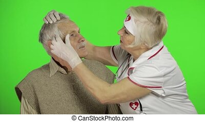 Kind mature woman nurse caregiver supporting to old elder man help with problem, female doctor therapist in uniform examines man and give treatment tips to senior patient