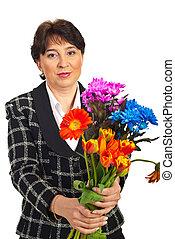 Mature woman offering flowers bouquet