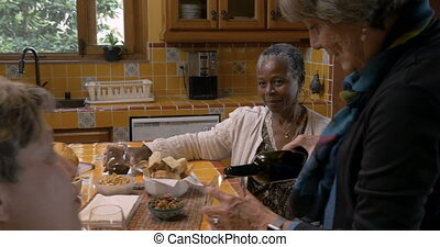 Mature woman over 60 pouring herself wine wearing a smart...