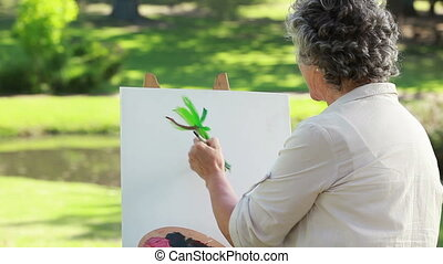 Mature woman painting on a canvas in the countryside