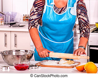 Mature woman pensioner knead dough at kitchen.