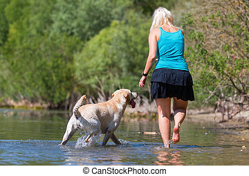 mature woman plays with a labrador in the lake