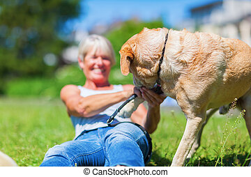 mature woman plays with her dog outdoors