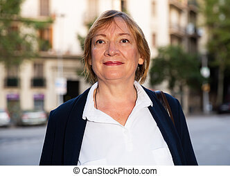 Mature woman posing in city center