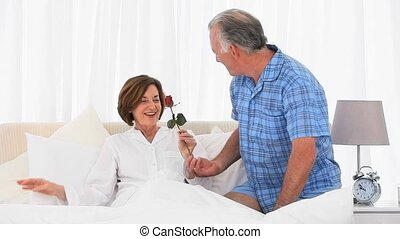Mature woman receiving a gift from her husband