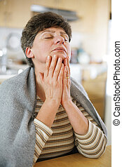 Mature woman relaxing with eyes closed.
