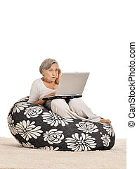 Mature woman relaxing with laptop