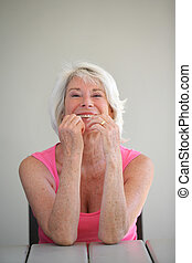 Mature woman sat in the garden laughing