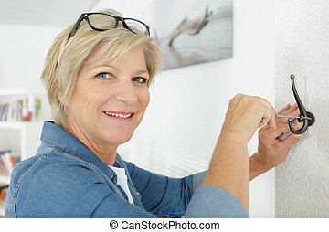 mature woman screwing a coat hook to the wall