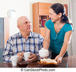 mature woman serving tea for her  man