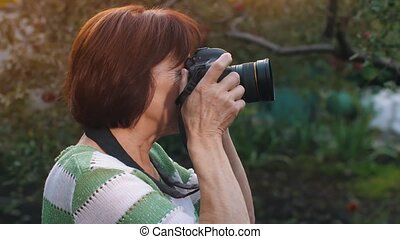 Mature woman shooting with photo camera - Portrait of mature...