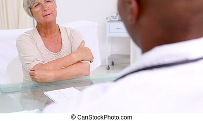 Mature woman showing her painful neck in the medical office