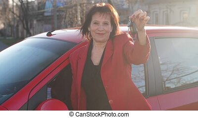 Mature woman showing keys near the car - Woman with new red ...