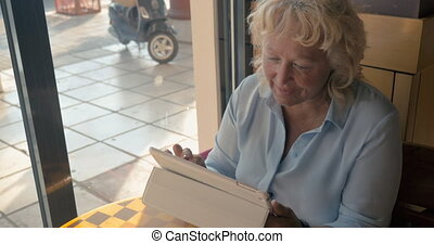 Mature woman sitting in a cafe and enjoys her tablet., outside the window the summer, sunny day
