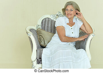 Mature woman sitting in vintage chair