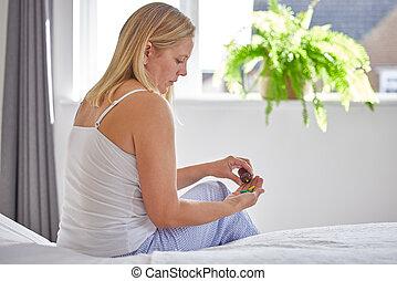 Mature Woman Sitting On Bed Wearing Pyjamas Taking ...