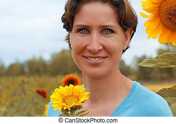 Mature woman standing in a sunflower field