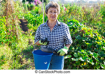 Mature woman standing in garden with horticultural instruments on day