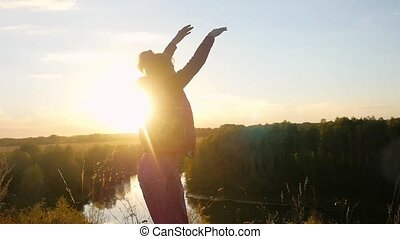 Mature woman standing on the rock rises her hands jumps...