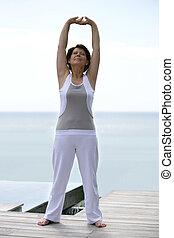 Mature woman stretching on a pontoon