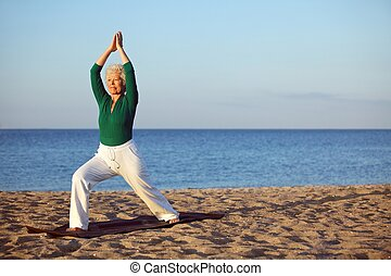 Mature woman stretching on the beach. Senior woman...