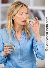 mature woman taking pills at home