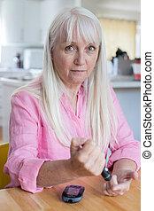 Mature Woman Testing Blood Sugar Level At Home