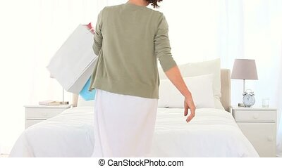 Mature woman testing her clothes in the bedroom