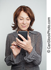 Mature woman texting on white background