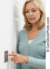 Mature Woman Turning Off Light Switch At Home