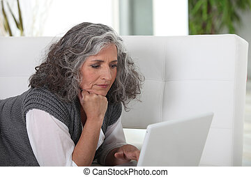 mature woman typing on her laptop