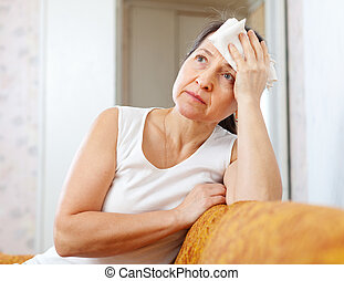 mature woman uses handkerchief on her head in home