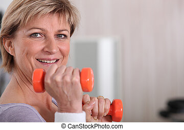 Mature woman using dumbbells