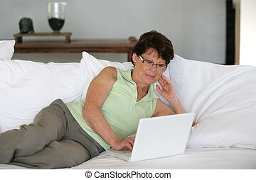 Mature woman using her laptop on a sofa