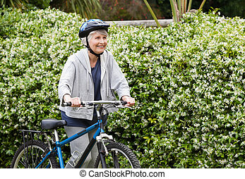 Mature woman walking with her mountain bike