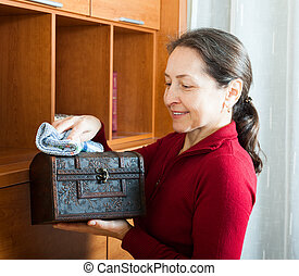 mature woman wiping dust from wooden chest at home