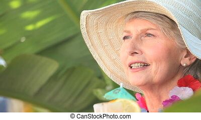 Mature woman with an hat holding a cocktail
