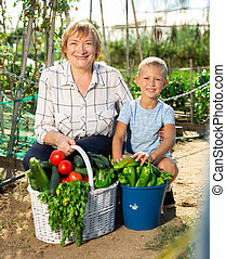 Mature woman with boy posing in garden