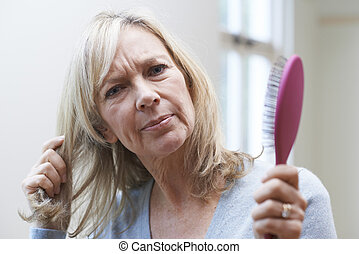 Mature Woman With Brush Corncerned About Hair Loss