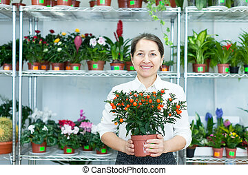 mature woman with citrus plant in  store