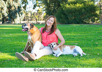 Mature woman with dog pets relaxed in park