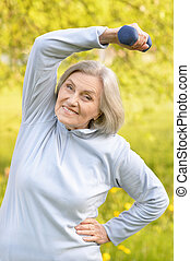 Mature woman with dumbbell