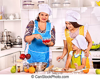Mature woman with family preparing at kitchen.