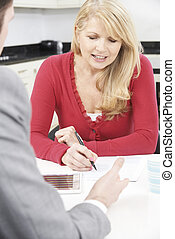 Mature Woman With Financial Advisor Signing Document At Home