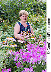 mature woman with flowers at garden