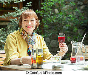 Mature woman  with  glass of red wine