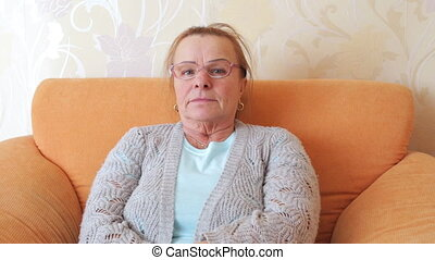 Mature woman with glasses looking thoughtfully at the camera